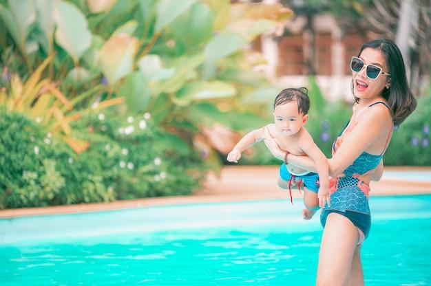 Aziatische moeder en zoontje genieten van zwemmen in een zwembad in de zomervakantie.