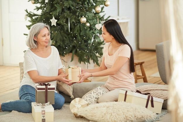 Aziatische moeder geeft kerstcadeau aan haar oudste dochter terwijl ze op de vloer in de kamer zitten met de kerstboom op de achtergrond