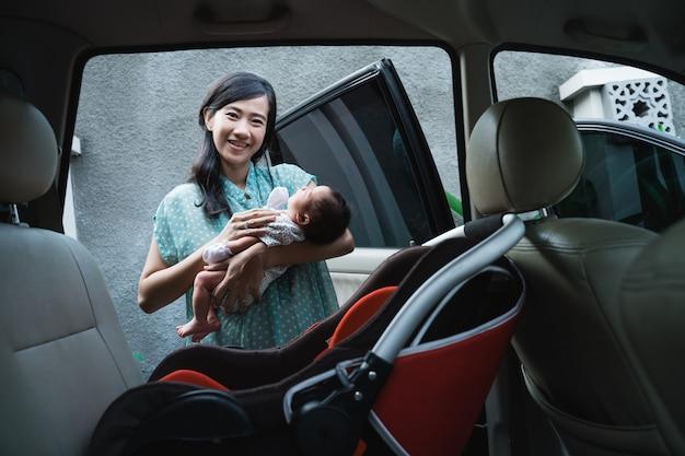 Aziatische moeder glimlach bij het dragen van haar dochtertje