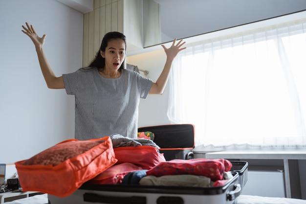 Aziatische moeder heeft hoofdpijn bij het bereiden van kleding en tassen