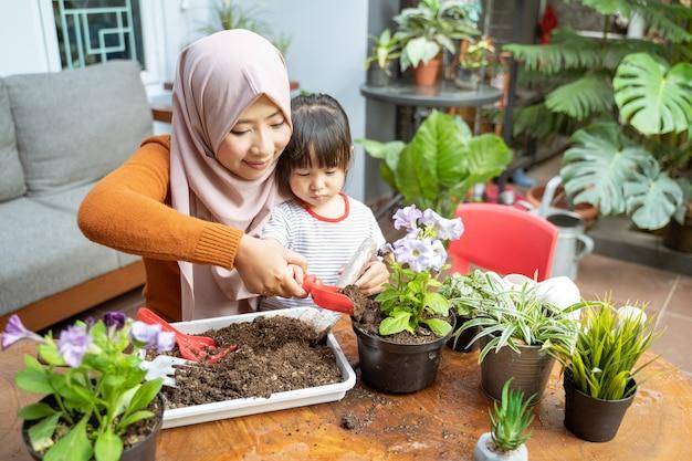 Aziatische moeder helpt haar dochter een kleine schop gevuld met aarde vast te houden om potplanten te laten groeien