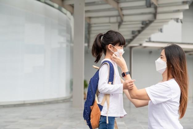 Aziatische moeder helpt haar dochter met het dragen van een medisch masker ter bescherming covid-19 of een uitbraak van het coronavirus om zich voor te bereiden om naar school te gaan als ze weer naar school gaat.