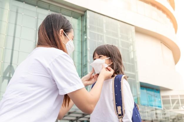 Aziatische moeder helpt haar dochter met het dragen van een medisch masker ter bescherming covid19-uitbraak