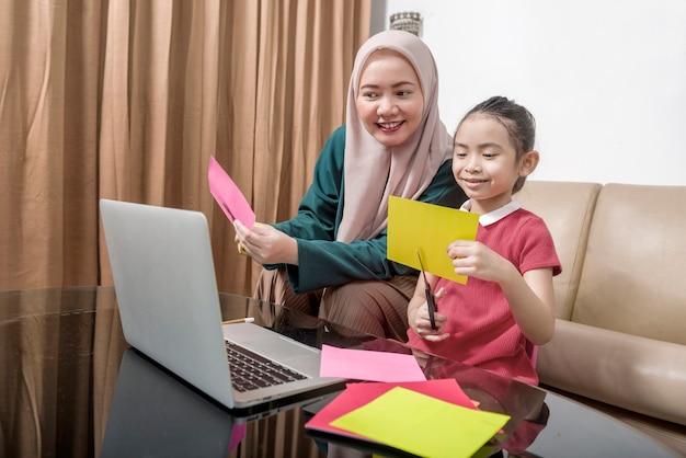 Aziatische moeder helpt meisje haar huiswerk met laptop thuis te doen. online onderwijs tijdens quarantaine