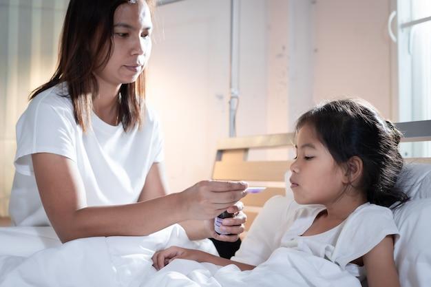 Aziatische moeder hoestsiroop geneeskunde op een lepel te geven aan haar dochter in bed