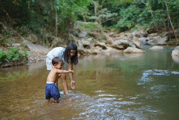 Aziatische moeder in blauw shirt met diy-borstzak speelwater met haar zoon van ongeveer 1 jaar en 9 maanden bij waterval