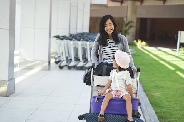 Aziatische moeder kijkt naar de camera tijdens het lopen duwen van de trolley