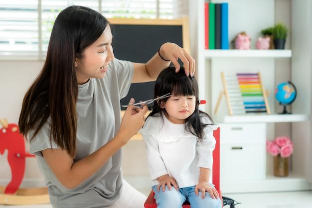 Aziatische moeder knippen haar naar haar dochter in de woonkamer thuis terwijl ze thuis veilig blijven van covid-19 coronavirus tijdens lockdown. zelfquarantaine en sociaal afstandsconcept.