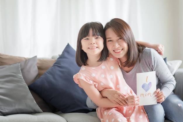 Aziatische moeder knuffel haar schattige dochter die handgemaakte wenskaart geeft met ik hou van moeder woord om haar thuis te verrassen