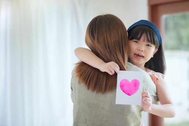 Aziatische moeder knuffel haar schattige dochter die handgemaakte wenskaart met kleurrijk hartsymbool geeft om haar thuis te verrassen