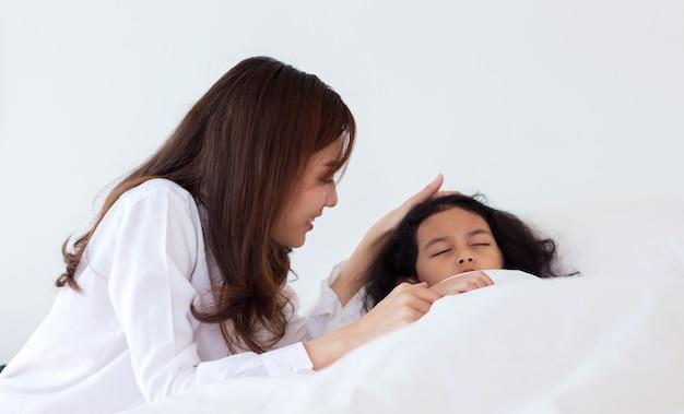 Aziatische moeder knuffelen en troosten van haar dochter en moedigt haar zieke dochter in de slaapkamer aan. concept van liefde en aanmoediging in het gezin