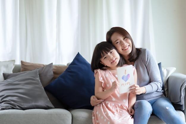 Aziatische moeder knuffelt haar schattige dochter die een handgemaakte wenskaart geeft met het woord 'i love mom' om haar thuis te verrassen