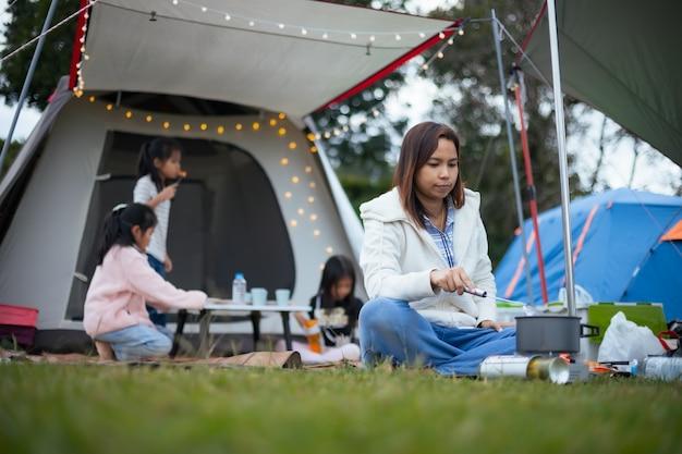 Aziatische moeder kookt voor familie buiten de tent terwijl ze met familie op de camping kampeert met geluk.