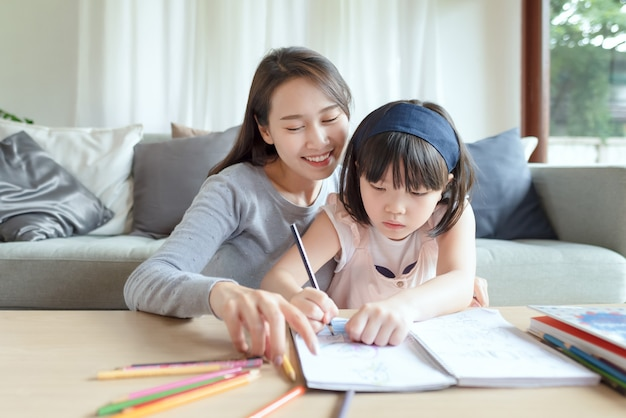 Aziatische moeder leert haar schattige dochtertje thuis in de woonkamer te studeren