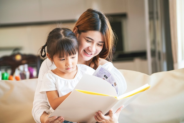 Aziatische moeder leesboek aan haar dochter thuis tijdens thuisonderwijs