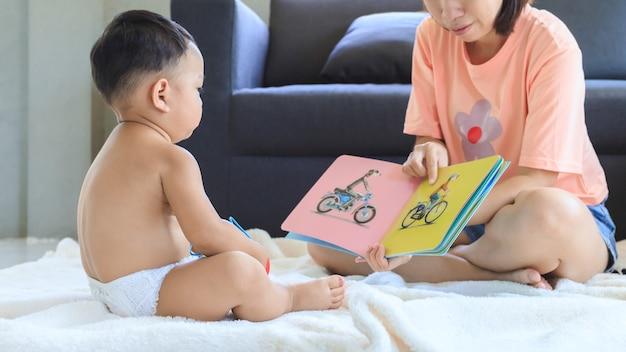 Aziatische moeder lesgeven en lezen van boek met haar schattige babyjongen thuis. familie en saamhorigheid concept