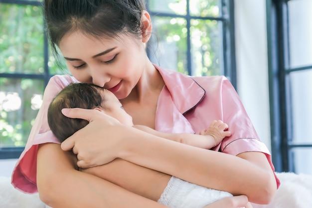 Aziatische moeder met een 1,5 maanden oud kind, leunend over haar schouder