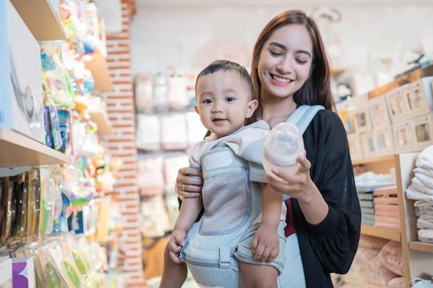 Aziatische moeder met haar peuterjongen die in de babywinkel winkelt
