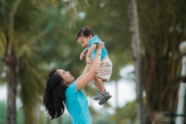 Aziatische moeder met haar zoon die pret heeft openlucht