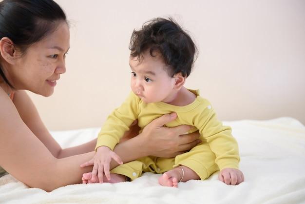 Aziatische moeder probeerde de schattige kleine baby op het bed te houden