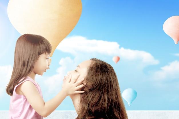 Aziatische moeder speelt met haar kleine meisje met kleurrijke luchtballon die met blauwe hemelachtergrond vliegt