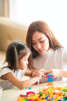 Aziatische moeder spelen houten blok speelgoed met haar dochter in de woonkamer thuis. aziatische familie- en kinderconcepten