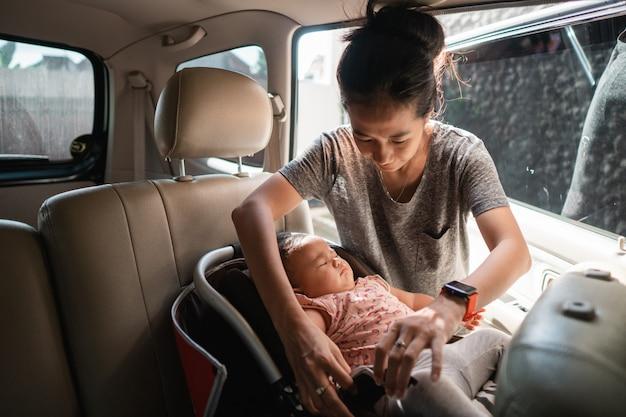 Aziatische moeder vastmakende kinderstoel
