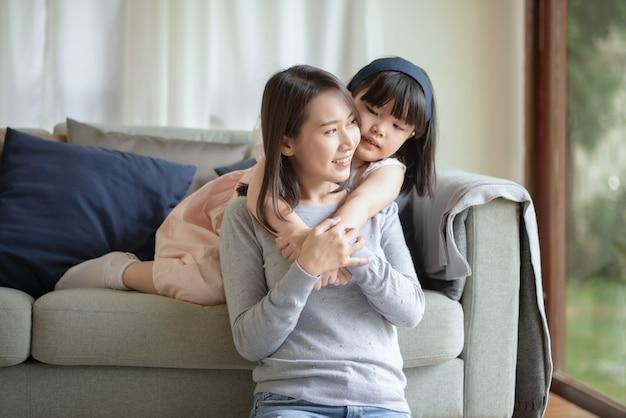 Aziatische moeder vrijt met warme knuffel haar schattige dochter thuis
