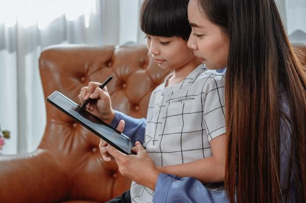Aziatische moeder werkt thuis samen met zoon. moeder leert kind voor online leeronderwijs. nieuwe normale levensstijl en gezinsactiviteit.