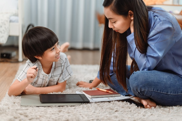 Aziatische moeder werkt thuis samen met zoon. moeder onderwijst kind voor online leeronderwijs. nieuwe normale levensstijl en gezinsactiviteit.