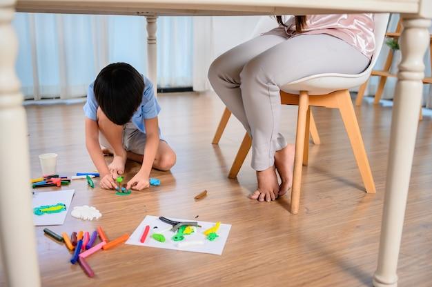 Aziatische moeder werkt thuis samen met zoon. moeder werkt online en kind speelt deeg onder tafel. vrouw levensstijl en gezinsactiviteit.