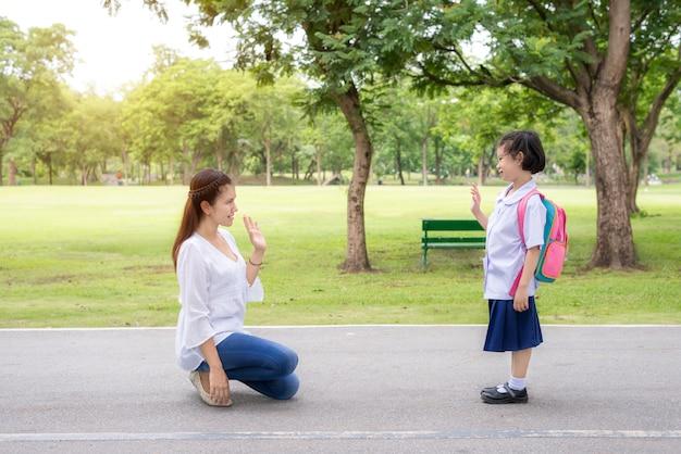 Aziatische moeder zegt vaarwel aan dochterstudent in park op school vóór studie.