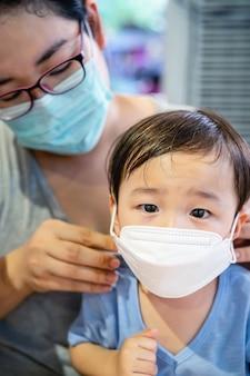 Aziatische moeder zetten een gezichtsmasker voor haar kind om mogelijke infectie in de supermarkt te voorkomen