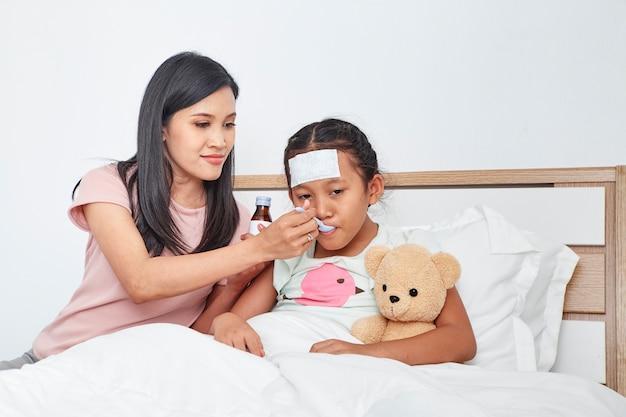 Aziatische moeder zorgen zieke dochter op bed
