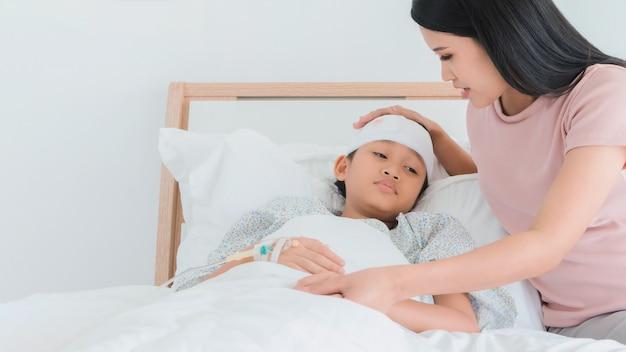 Aziatische moeder zorgt voor dochter gewond aan hoofd en blijf op bed in het ziekenhuis.
