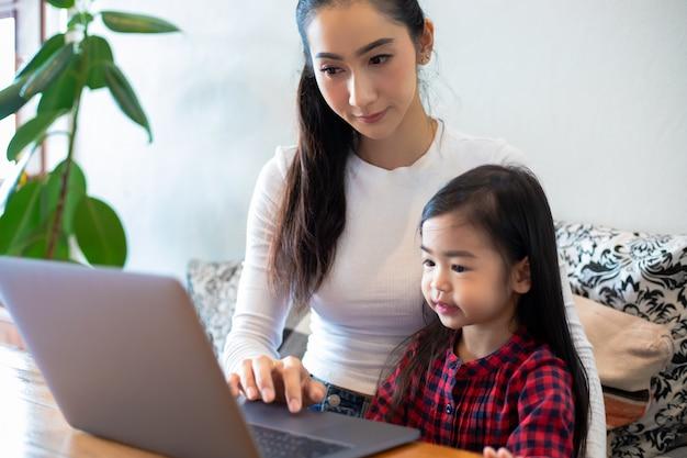 Aziatische moeders leren hun dochters thuis een boek te lezen en notitieboekjes en technologie te gebruiken voor online leren tijdens schoolvakanties. educatieve concepten en activiteiten van het gezin