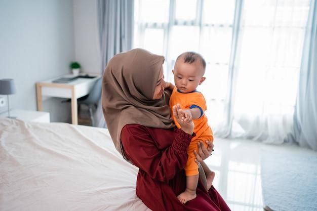 Aziatische mohammedaanse moeder die haar zoontje op schoot bij het spelen samen