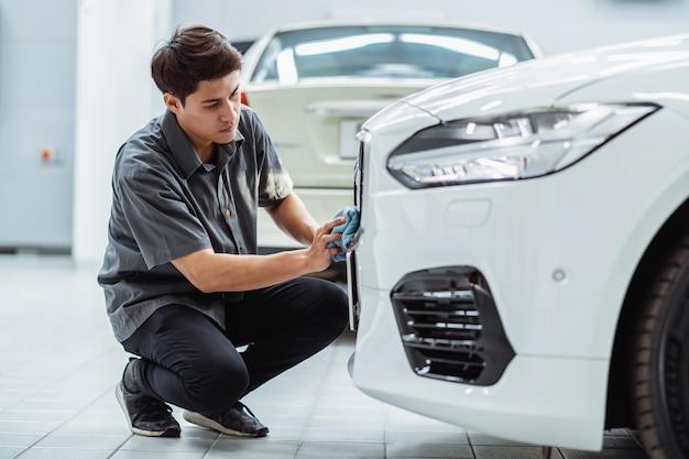 Aziatische monteur die de auto schoonmaakt in onderhoudservicecentrum dat een deel van toonzaal is