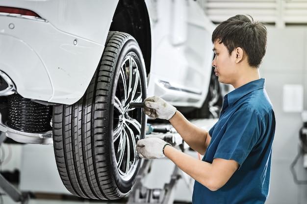 Aziatische monteur die de autowielen in onderhoudscentrum controleert en herstelt