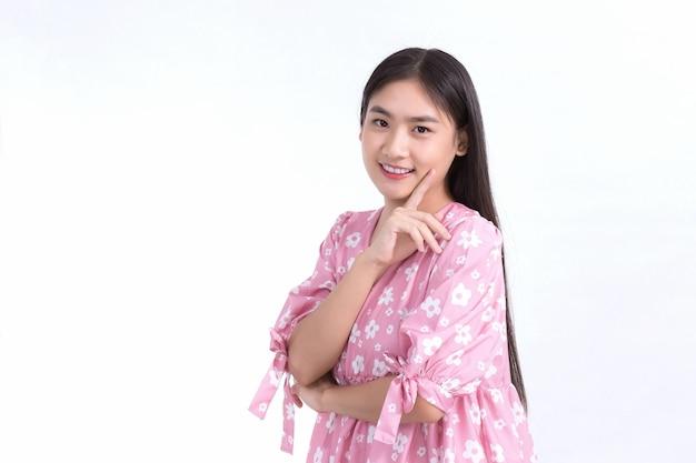 Aziatische mooi meisje in roze jurk en zwart lang haar. haar handen raken de wangglimlach aan, tonen een mooie huid op een witte achtergrond.