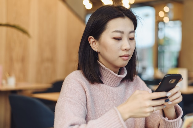 Aziatische mooi meisje klimmen op de telefoon in een koffieshop. een mooie vrouw zoekt informatie op internet of werkt