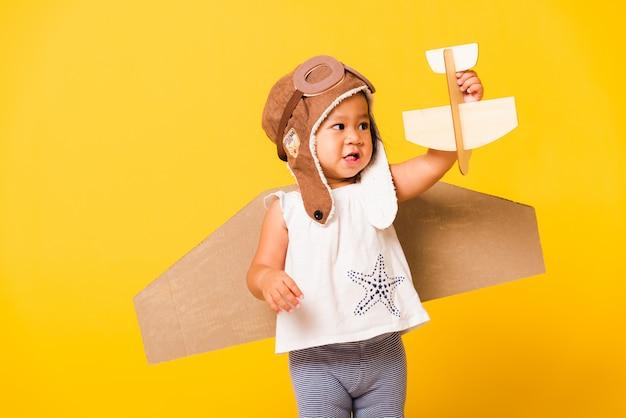 Aziatische mooie baby meisje glimlach slijtage pilootmuts met speelgoed kartonnen vliegtuig vleugels vliegen houd vliegtuig speelgoed