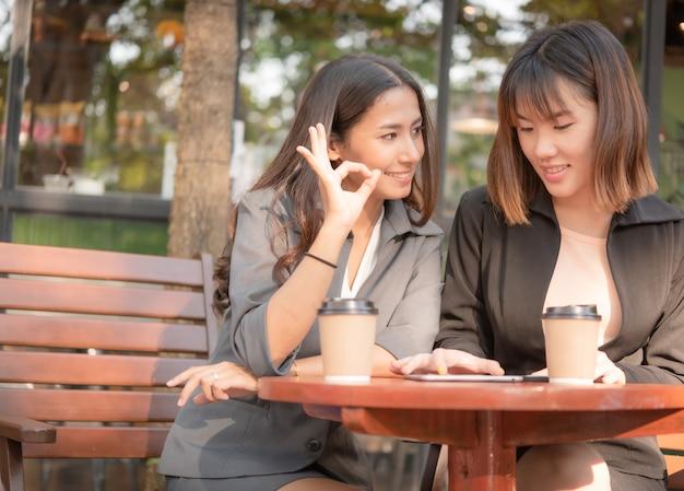 Aziatische mooie bedrijfsvrouw die met tablet en smartphone in de winkel van de koffiekoffie werken