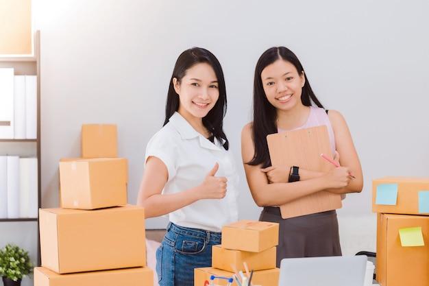 Aziatische mooie empower vrouw en vriend thuis werken met online business shop. eigenaar zakenvrouw opstarten met accepteren bestellingen.