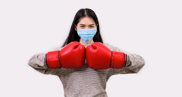 Aziatische mooie gelukkige jonge vrouw die maskerbescherming en bokshandschoenen draagt, maakt zich klaar voor de strijd tegen het coronavirus, met kopie ruimte