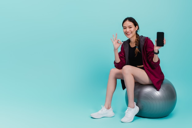 Aziatische mooie gelukkige smartphone van de vrouwenholding en het zitten op geschikte bal na oefening die op blauw wordt geïsoleerd