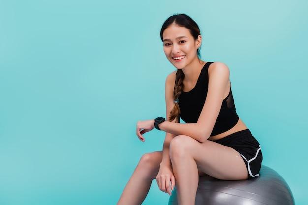 Aziatische mooie gelukkige vrouwenzitting op geschikte bal na oefening