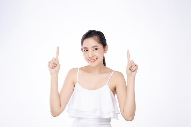 Aziatische mooie jonge vrouw die beide hand met vinger aan bovenkant met glimlachgezicht richt
