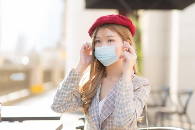 Aziatische mooie jonge vrouw die een pak en een rode dop draagt, draagt een medisch gezichtsmasker in de gezondheidszorg, vervuiling pm2.5, nieuw normaal en coronavirusbeschermingsconcept.