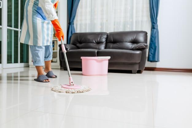 Aziatische mooie jonge vrouw in beschermende handschoenen met behulp van een platte natte mop tijdens het schoonmaken van de vloer in het huis
